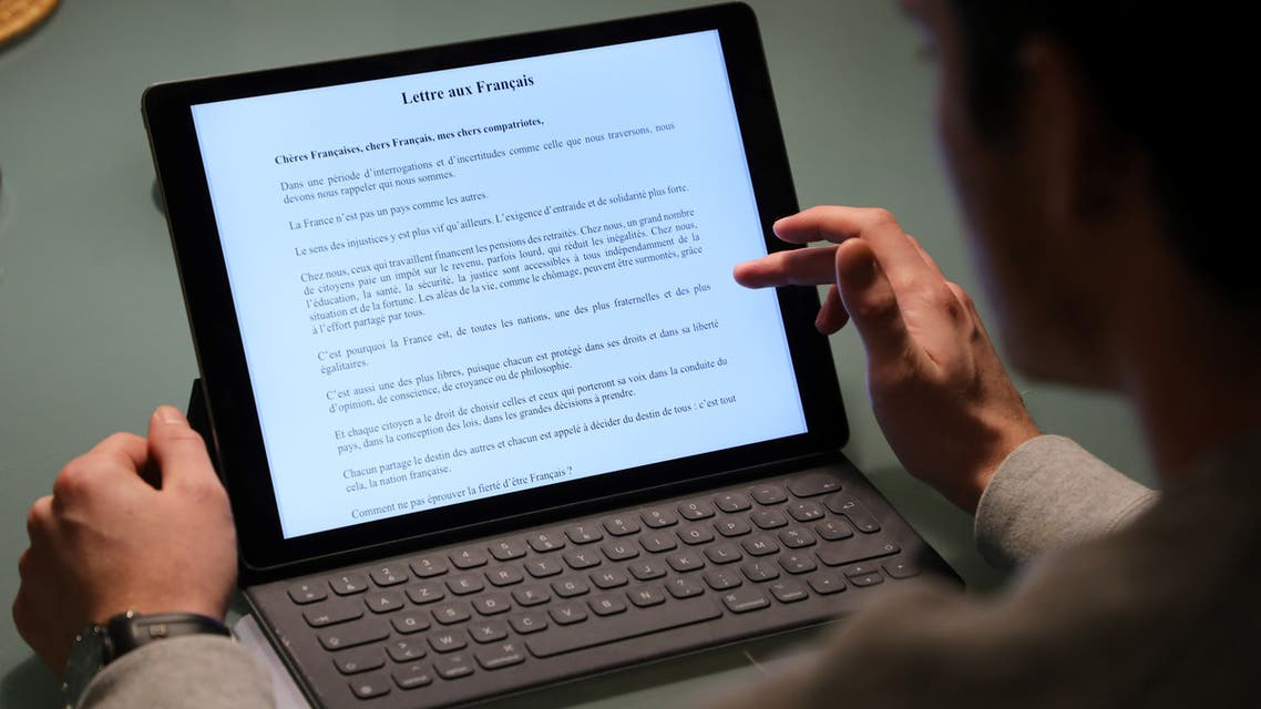 """A man reads a portion of a """"Letter to the French People"""" (Lettre aux Francais) written by French President Emmanuel Macron, on January 13, 2019, in Paris. Macron published a personal letter to households spelling out his goals for the """"great national debate"""", a public consultation beginning on January 15, 2019, to discuss the """"essential questions"""" facing the nation after nearly two months of violent so-called yellow vest protests."""