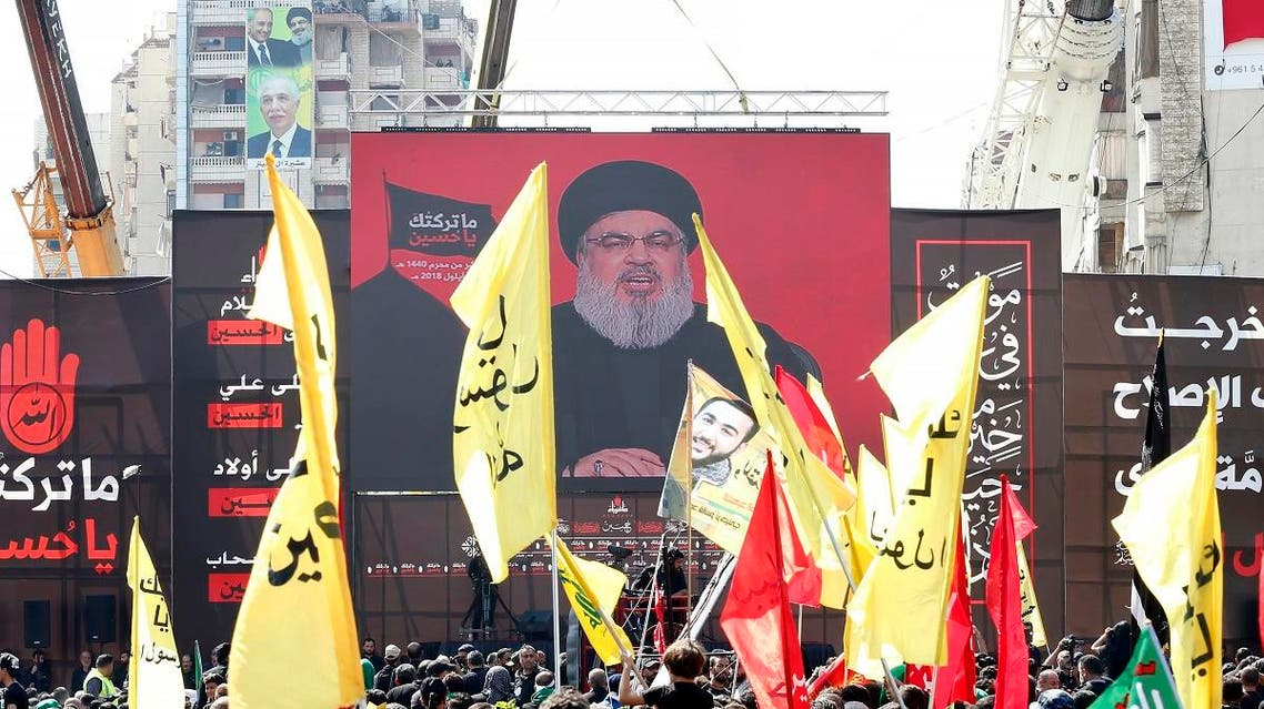 Supporters of Lebanon's Shiite movement Hezbollah gather near a giant poster of their leader Hassan Nasrallah during a ceremony to mark Ashura on September 20, 2018 in Beirut. Ashura commemorates the death of Imam Hussein, grandson of the Muslim faith's prophet Mohammed, who was killed by the armies of his rival Yazid over the succession for the caliphate near Karbala in 680 AD. ANWAR AMRO / AFP