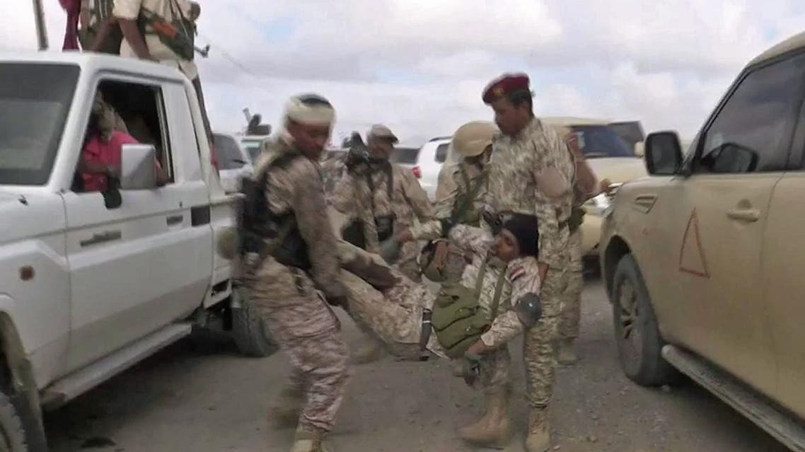 An image grab taken from a video obtained by AFPTV shows a wounded Yemeni soldier being carried by comrades after a drone exploded above Yemen's al-Anad airbase. (AFP)