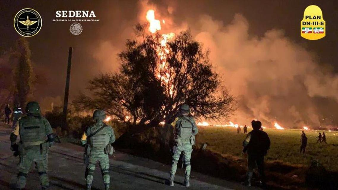 Military personnel watch as flames engulf an area after a ruptured fuel pipeline exploded, in the municipality of Tlahuelilpan, Hidalgo. (Reuters)
