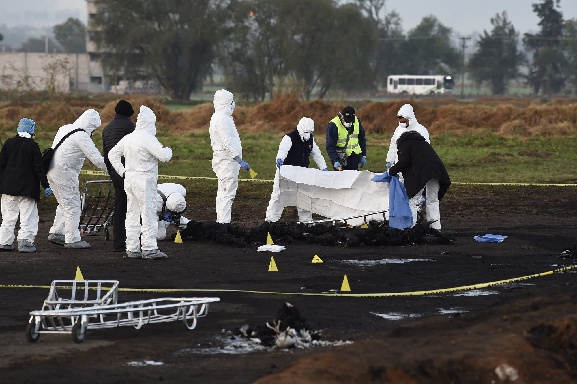 Forensic experts cover the burned remains of some of the victims of a massive blaze triggered by a leaky pipeline in Mexico on January 19, 2019. (AFP)