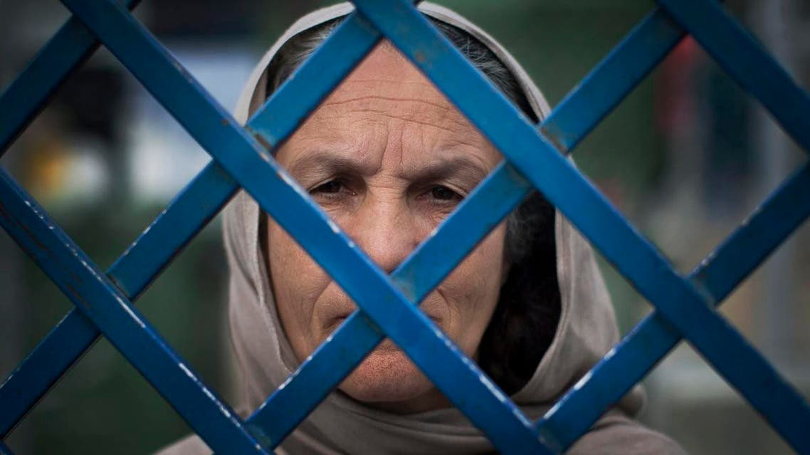 Picture taken March 28, 2013 shows Afghan female prisoner Fauzia steering out of the prison bars at Badam Bagh, Afghanistan's central women's prison, in Kabul, Afghanistan.(AP)