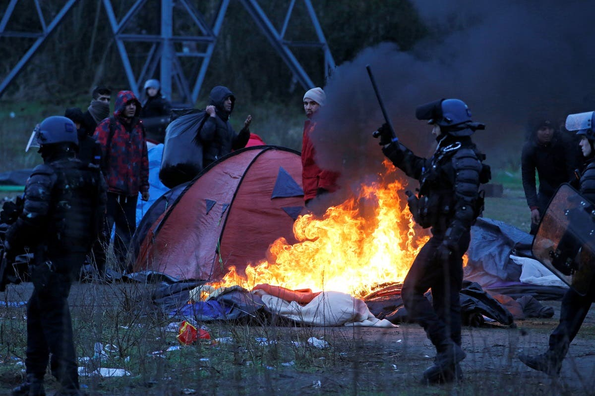 A burning tent is seen, as French riot police push back Iranian Kurdish migrants, during the dismantling of a camp in Calais. (Reuters)