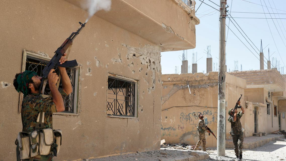 FILE PHOTO: Kurdish fighters from the People's Protection Units (YPG) fire rifles at a drone operated by Islamic State militants in Raqqa, Syria, June 16, 2017. REUTERS/Goran Tomasevic/File Photo
