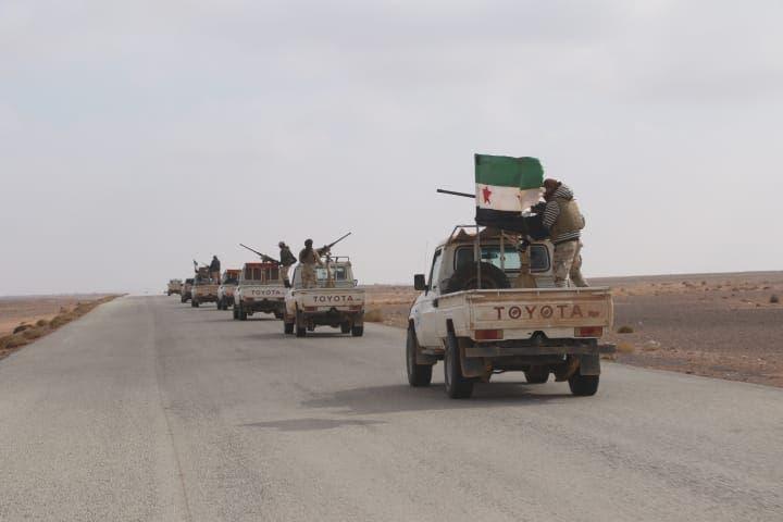 مقاتلون من المعارضة المسلّحة بالقرب من المخيم