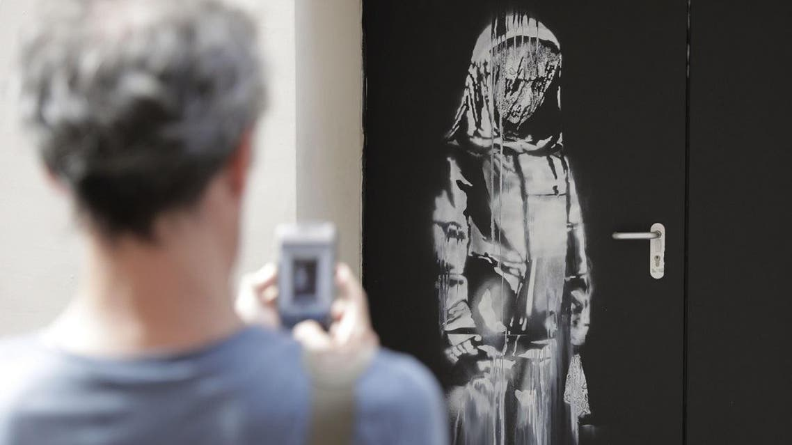 In this file photo taken on June 25, 2018, a man takes a photograph of an artwork by street artist Banksy in Paris on a side street to the Bataclan concert hall where a terrorist attack killed 90 people on Novembre 13, 2015. (AFP)