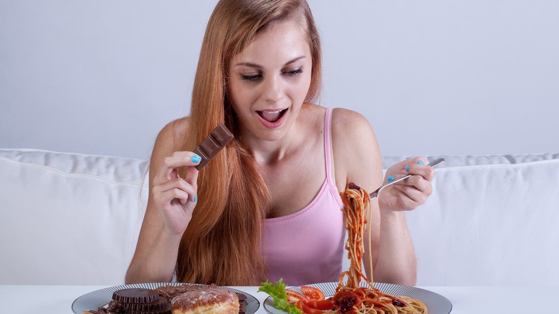 Girl suffering from bulimia eats dinner - Stock image