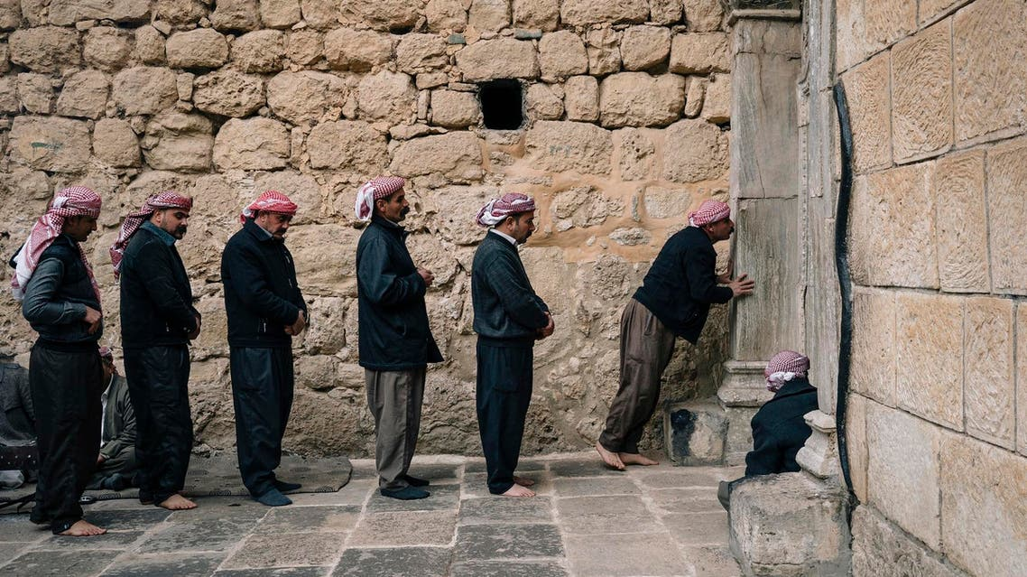 Men stand in line to enter a temple in Lalish, the holiest site of the Yazidi religion. (AFP)