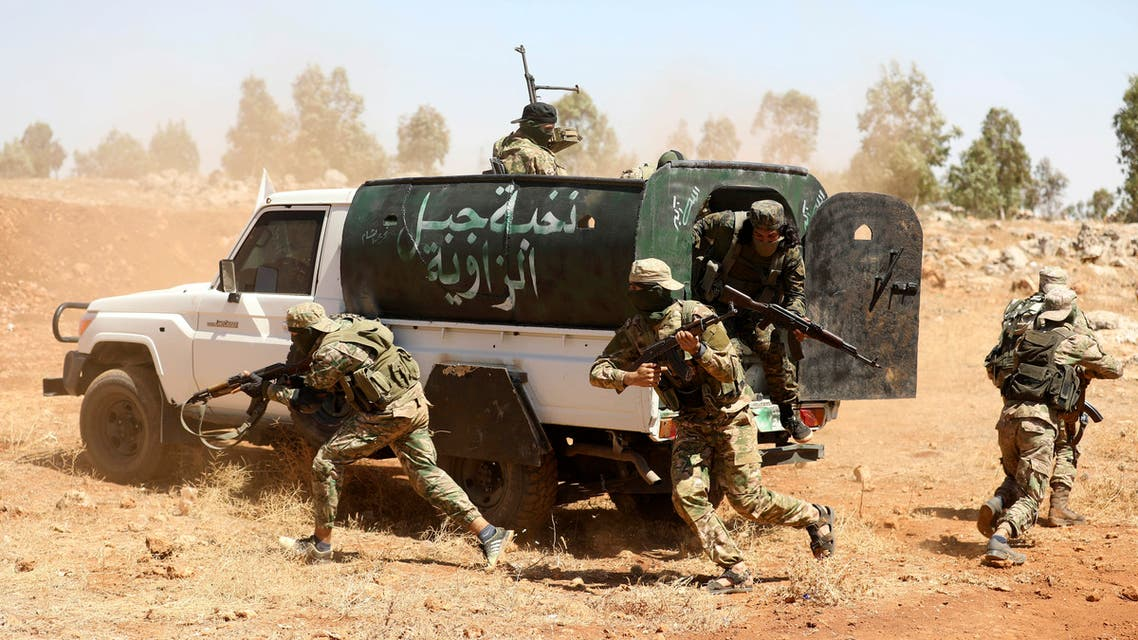Syrian fighters attend a mock battle in anticipation of an attack by the regime on Idlib province and the surrounding countryside, during a graduation of new Hayat Tahrir al-Sham (HTS) members at a camp in the countryside of the northern Idlib province on August 14, 2018.
