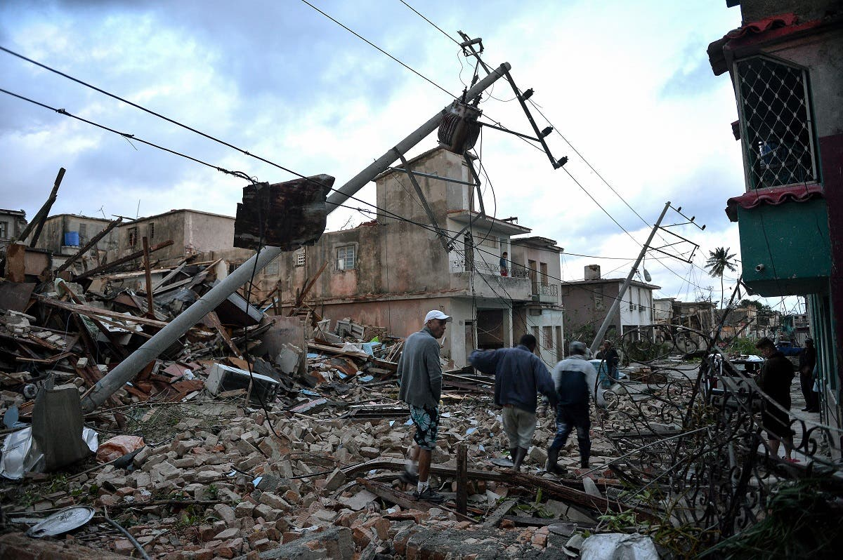 Residents walk amid the debris of buildings left after the passage of a tornado in Havana, on January 28, 2019. (AFP)