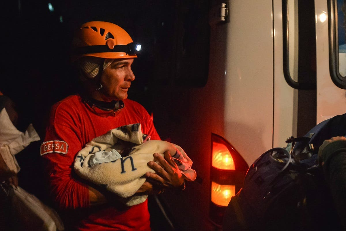 Firefighter holding a baby after a tornado hit Havana, on January 28, 2019. (AFP)