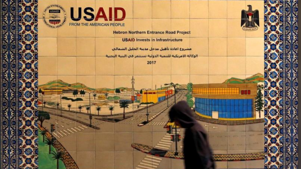 A Palestinian walks past a ceramic sign of a U.S. Agency for International Development (USAID) project in Hebron in the Israeli-occupied West Bank January 31, 2019. Picture taken January 31, 2019. (Reuters)