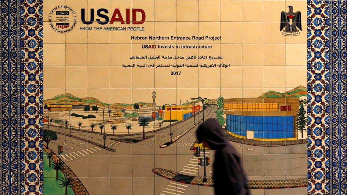 فلسطيني يمر أمام لافتة مشروع للوكالة الأميركية للتنمية الدولية في الضفة الغربية