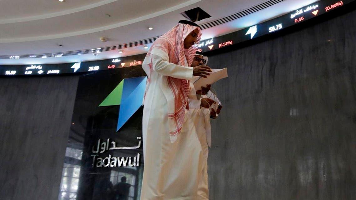 Saudi men walk at the Tadawul Saudi Stock Exchange in Riyadh. (Reuters)