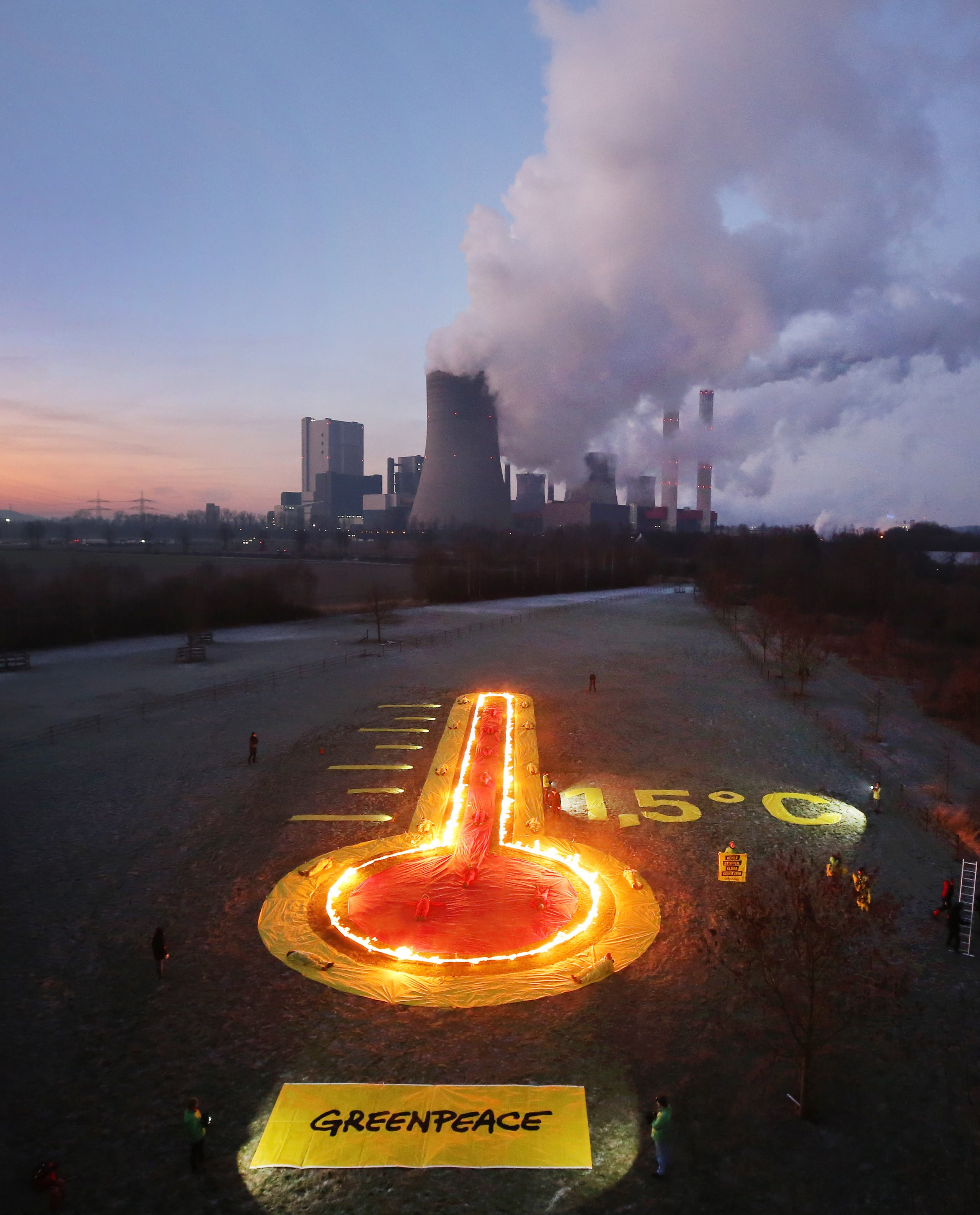 Greenpeace activists have set up an installation depicting a thermometer in front of the Niederaussem lignite-fired power station in Rommerskirchen, western Germany, in a protest on January 22, 2019 against the burning of fossil fuels provoking global warming, asking to limit the rise of global temperatures to 1,5 degrees Celsius.