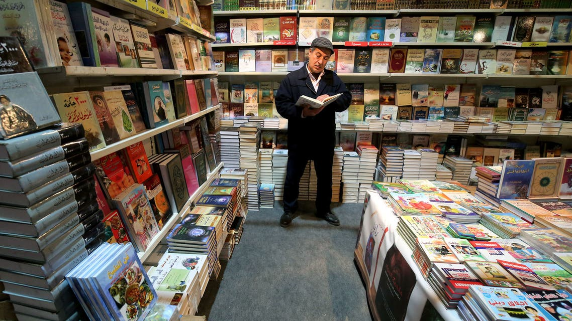 An Iraqi man reads during the opening of the International Book Fair in Baghdad on February 07, 2019.
