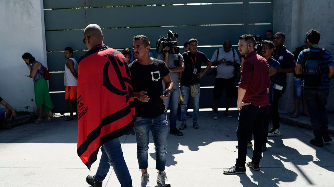 Friends, fans and journalists stand at the entrance of the Flamengo soccer training center as they wait for information after a fire in the facilities of the soccer club in Rio de Janeiro, Brazil, Friday, Feb. 8, 2019 (AP)