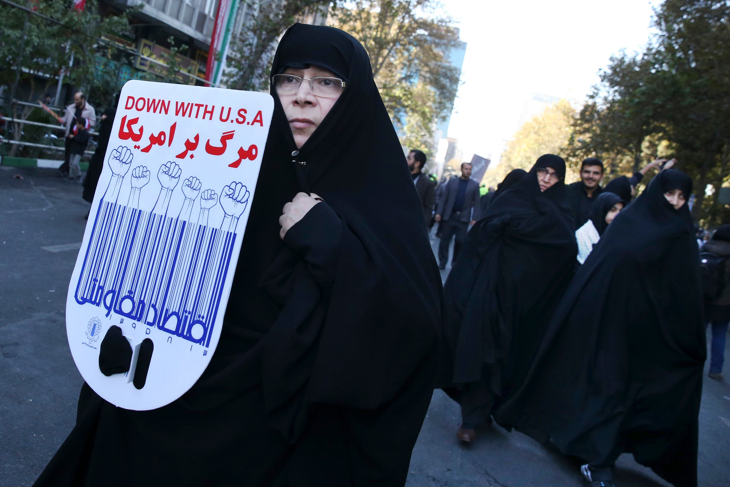 An Iranian demonstrator holds an anti-US poster in a state-organized annual rally in front of the former US Embassy in Tehran in 2016 on the 37th anniversary of the seizure of the embassy by militant Iranian students. (AP)