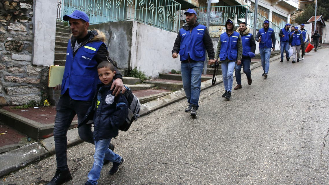 Members of the Palestinian Youth Against Settlements (YAS) activists escort a child on his way to school in the occupied West Bank town of Hebron, on February 10, 2019. The YAS activists have been monitoring areas in Hebron following Israel's decision not to renew the mandate of Temporary International Presence in Hebron (TIPH) group in the occupied West Bank city.