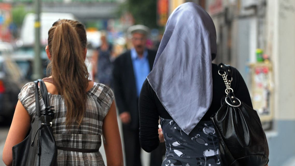Two women, one being veiled (R), walk along a street in the Berlin district of Kreuzberg - Neukoelln on July 16, 2009. Around 120,000 Turks live currently in Berlin, which has a total population of 3.4 millions. AFP PHOTO KAVEH ROSTAMKHANI