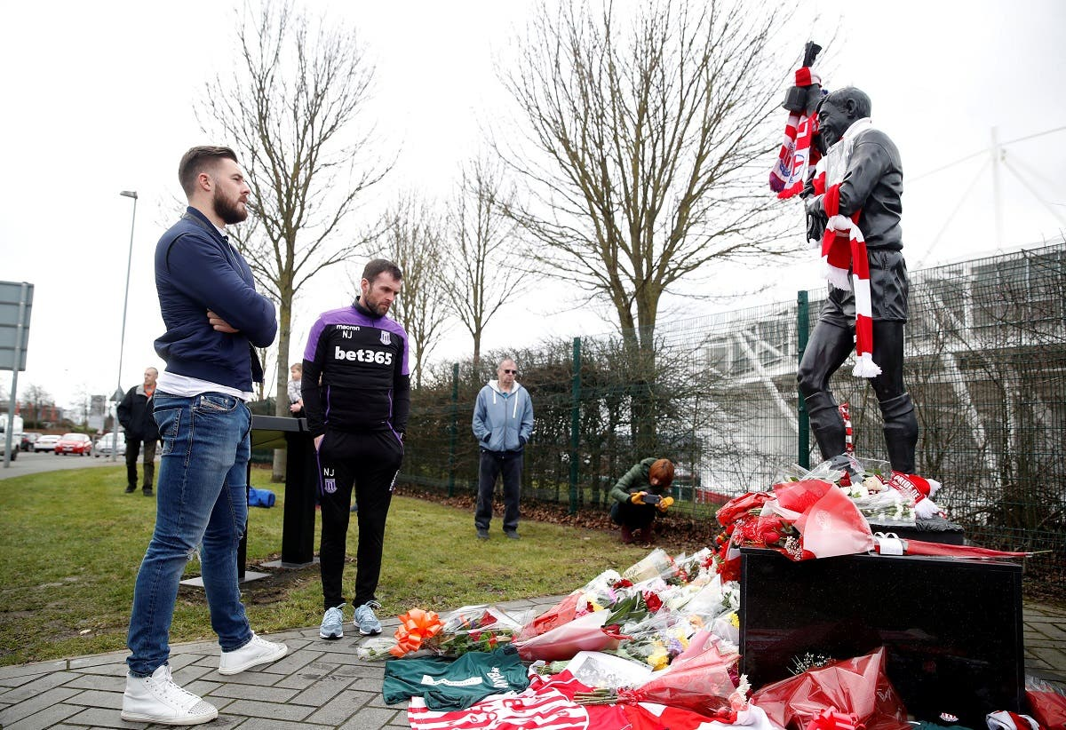 Stoke City's Jack Butland and manager Nathan Jones as tributes are placed on a statue of Gordon Banks outside the stadium. (Reuters)