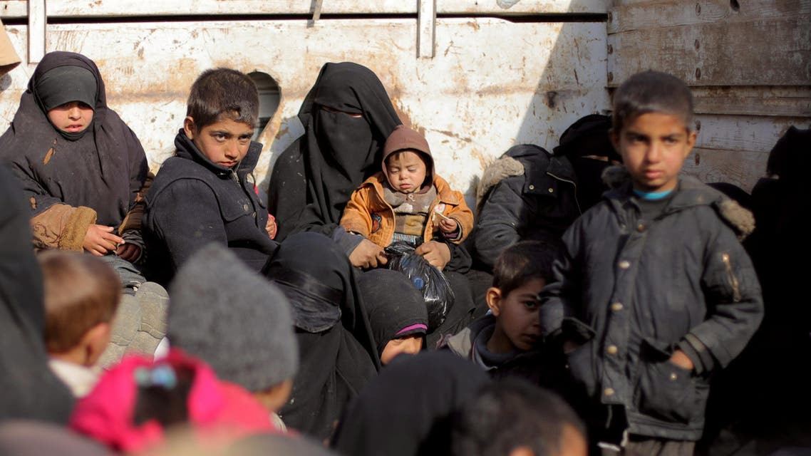 Women and children fleeing the battered Islamic State-held holdout of Baghouz in the eastern Syrian province of Deir Ezzor walk with covers and suitcases into a nearby area held by the Syrian Democratic Forces (SDF) on February 12, 2019.
