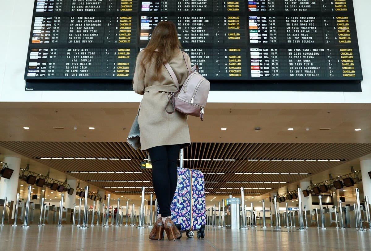 A stranded passenger looks at a flight information board displaying cancelled flights during a strike by Belgian trade unions at Zaventem international airport near Brussels on February 13, 2019. (Reuters)