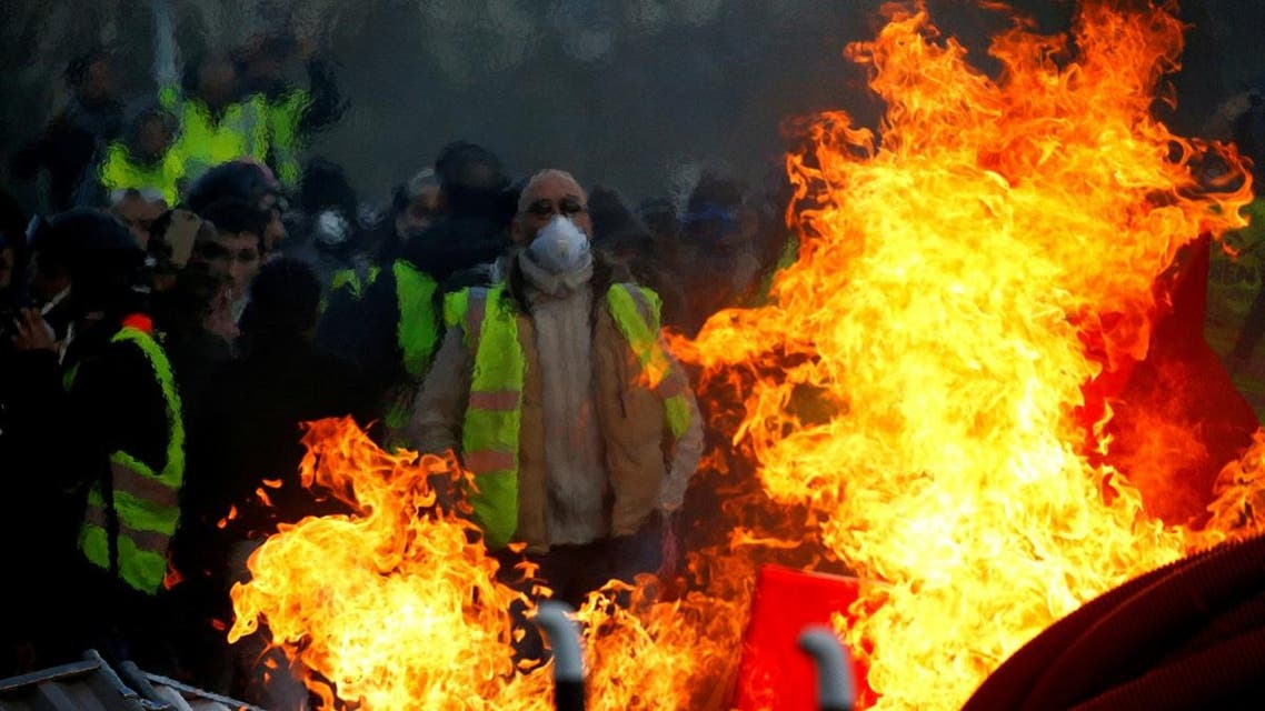"""Protesters wearing yellow vests are seen behind a fire as they attend a demonstration of the """"yellow vests"""" movement in Angers, France. (Reuters)"""
