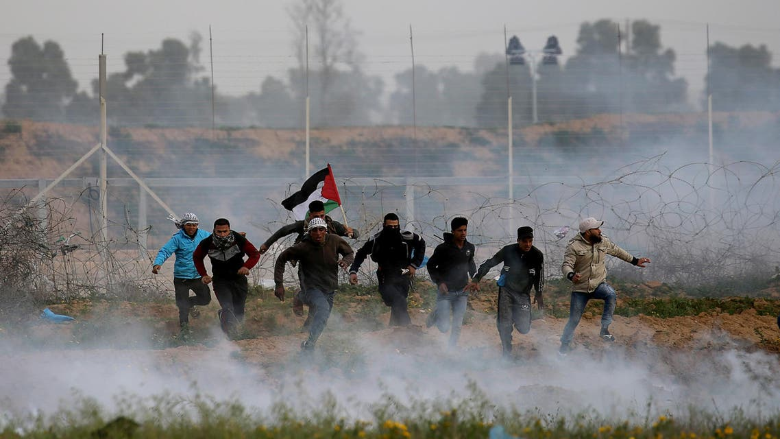 Palestinian demonstrators run away from Israeli fire and tear gas during a protest at the Israel-Gaza border fence, in the southern Gaza Strip February 15, 2019. REUTERS/Ibraheem Abu Mustafa TPX IMAGES OF THE DAY