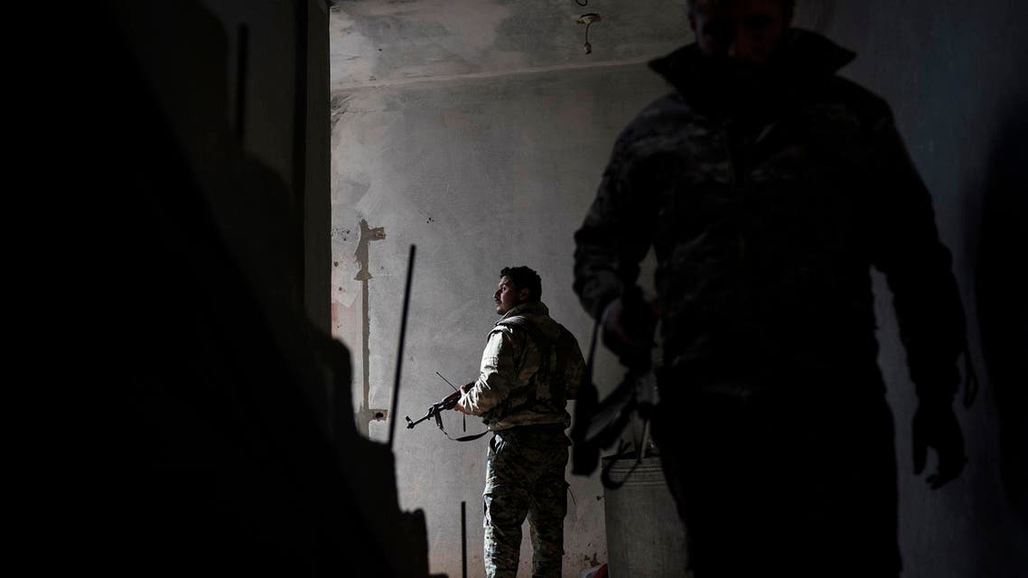 Syrian Democratic Forces fighters walk in a building on Saturday, February 16, 2019, as the fight against ISIS continues in the village of Baghouz, Syria. (AP)