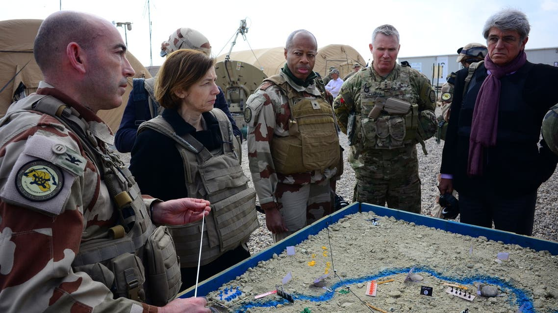 (L to R) French Major of the Wagram Task Force Francois-Regis Legrier explains military positions on a sand map to French Defence Minister Florence Parly, French General Jean-Marc Vigilant, US Army General Paul La-camera, and French ambassador to Iraq Bruno Aubert, at a French artillery forward operating base (FOB) near al-Qaim in Iraq's western Anbar province opposite Syria's Deir Ezzor region, a few kilometres away from the last scrap of territory held by IS, on February 9, 2019.