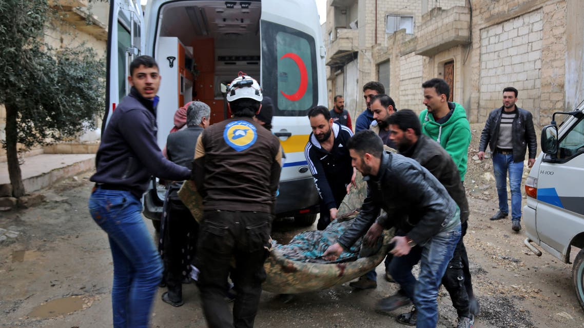 """A member (3rd-L) of the Syrian Civil Defence (also known as """"The White Helmet"""") carries a wounded woman following a strike in the town of Khan Shaykhun in the southern countryside of the rebel-held Idlib province, on February 15, 2019."""