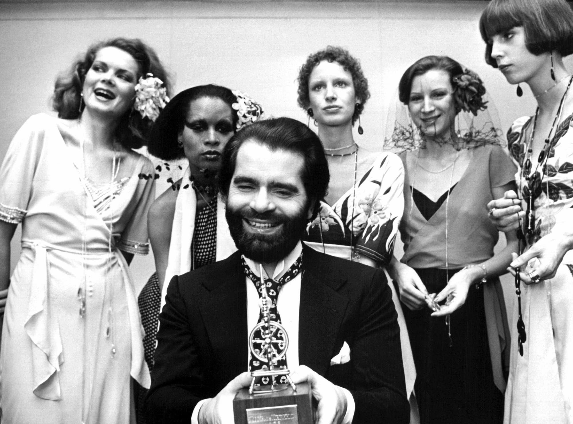 German fashion designer Karl Lagerfeld posing with models after receiving an award in Krefeld, western Germany, on November 29, 1973. (AFP)