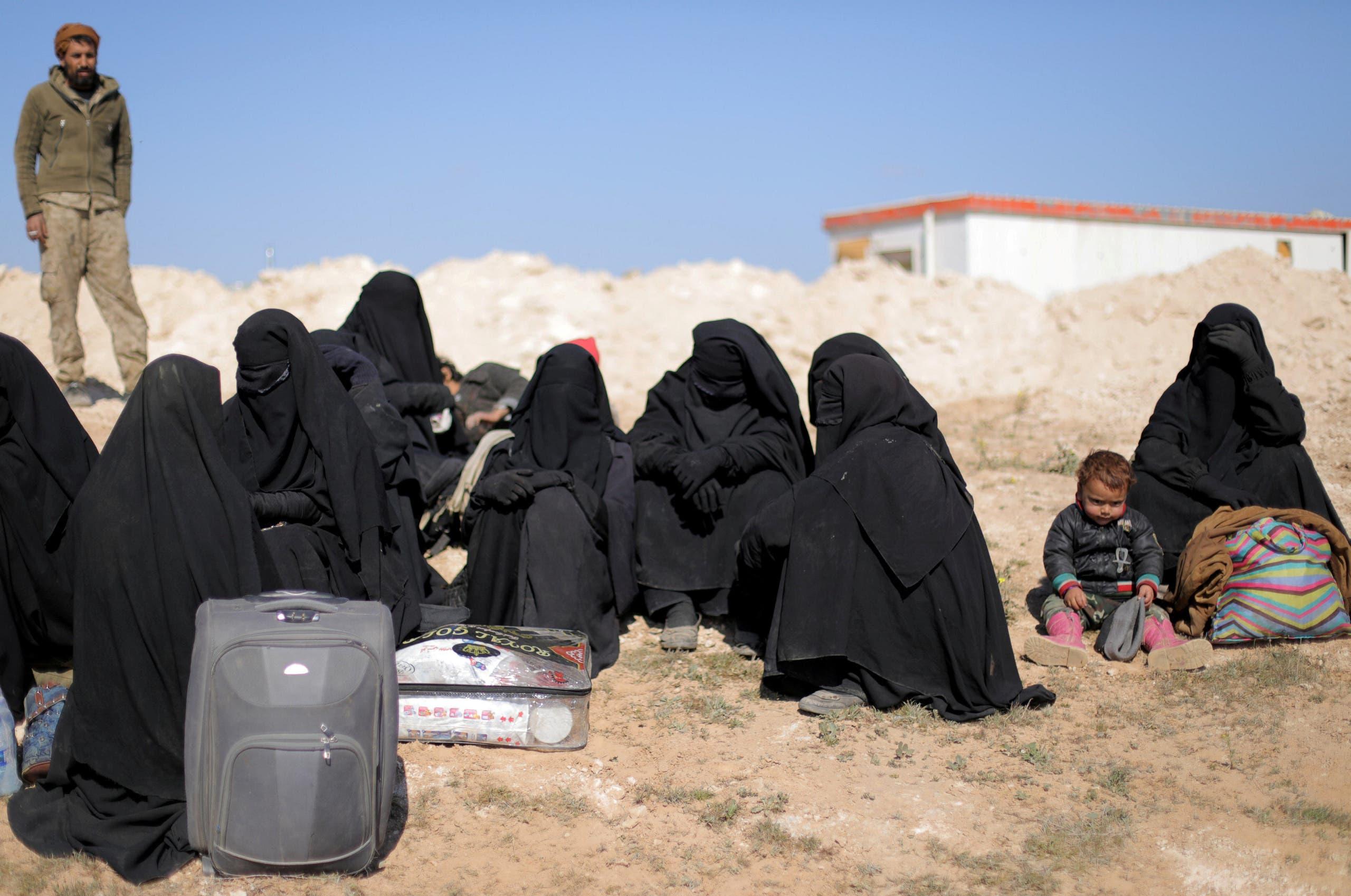 نساء ينتظرن مع أغراضهن بالقرب من الباغوز