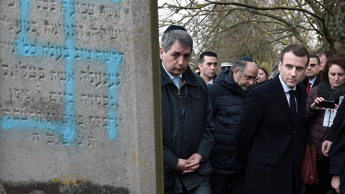 French President Emmanuel Macron looks at a grave vandalized with a swastika during a visit at the Jewish cemetery in Quatzenheim on February 19, 2019. (Reuters)