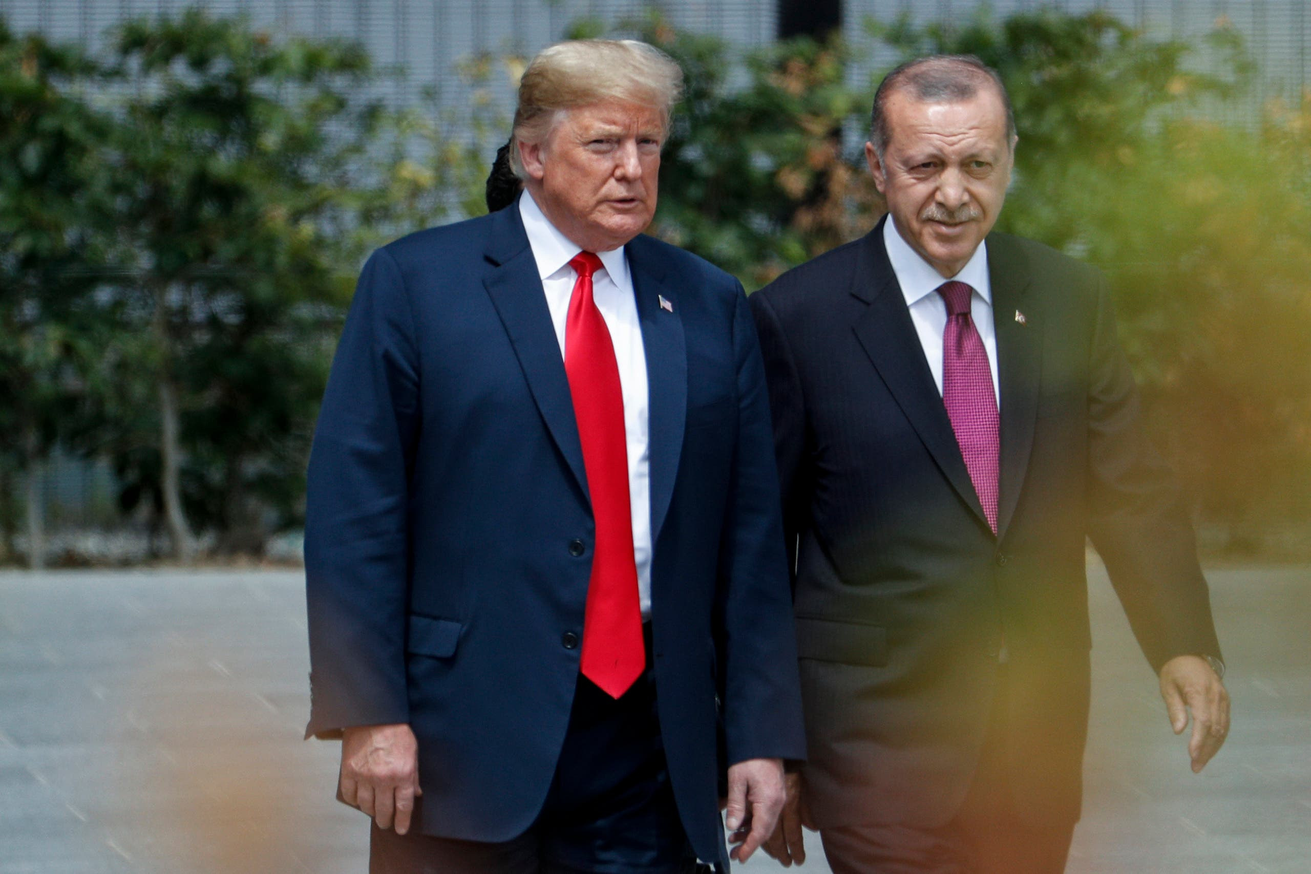 US President Donald Trump (L) speaks to Turkey's President Recep Tayyip Erdogan during the opening ceremony of the NATO (North Atlantic Treaty Organization) summit, at the NATO headquarters in Brussels, on July 11, 2018. (AFP)
