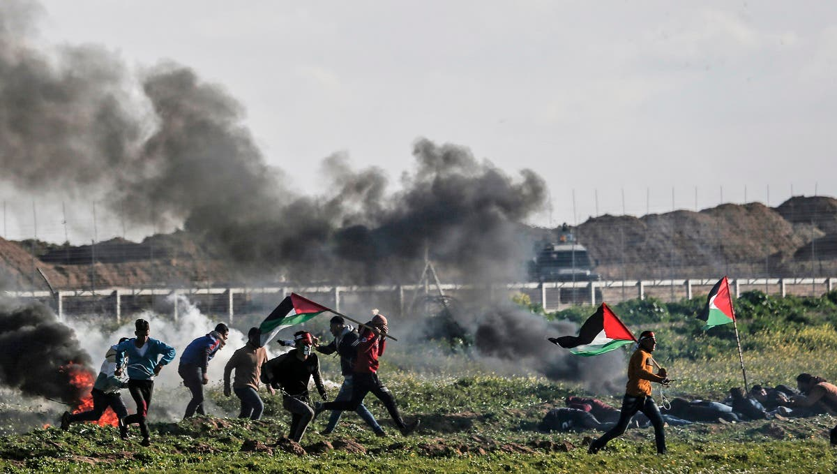 Palestinian protesters holding national flags walk past burning tires during a demonstration near the fence along the border with Israel, east of Gaza City, on February 22, 2019. (AFP)