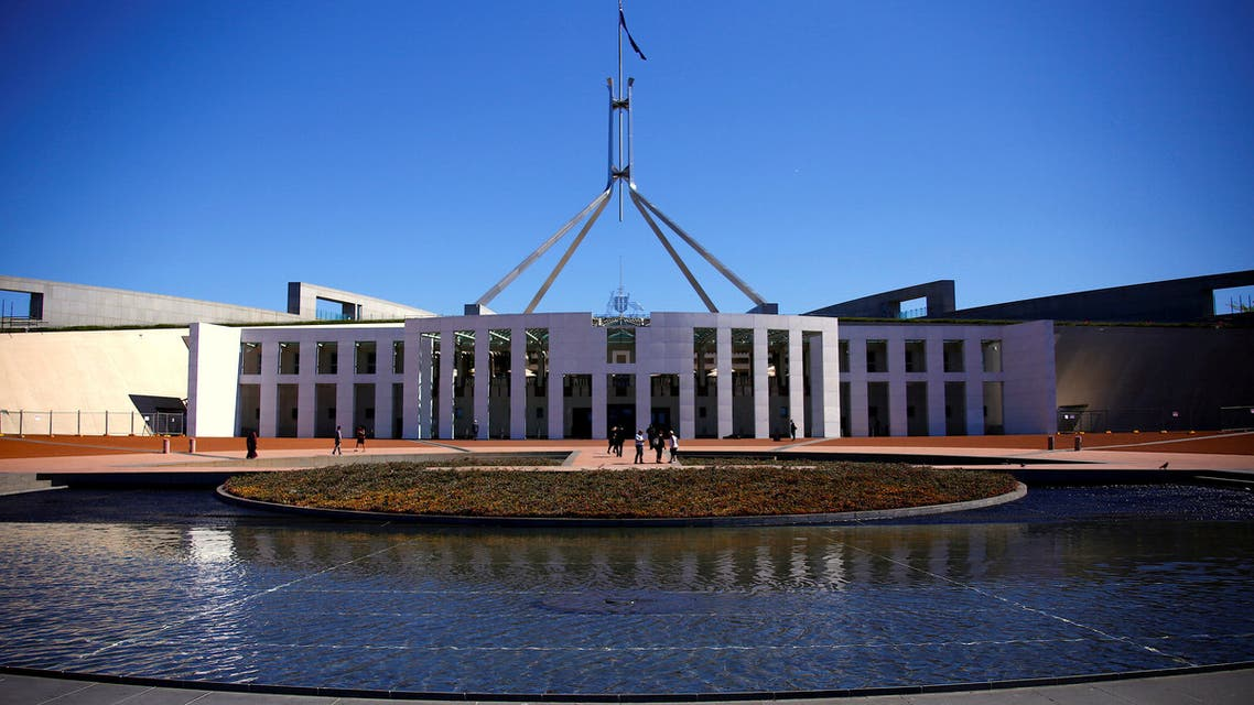 FILE PHOTO - Tourists walk around the forecourt of Australia's Parliament House in Canberra, Australia, October 16, 2017. REUTERS/David Gray/File Photo