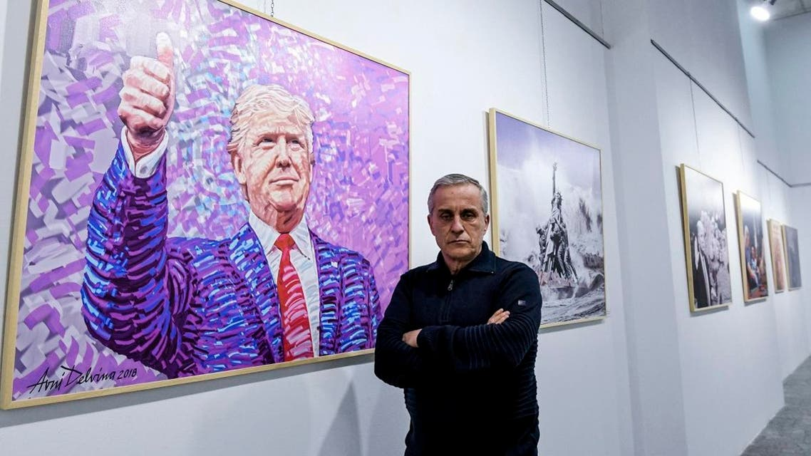 Albanian artist Avni Delvina poses for a photo in front of his paintings during the exhibition 'The Donald' in Tirana. (AFP)
