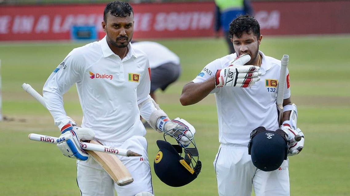 Sri Lanka's Oshada Fernando (L) and Kusal Mendis walk back to the pavilion after victory in the second Test cricket match between South Africa and Sri Lanka in Port Elizabeth on February 23, 2019. (AFP)