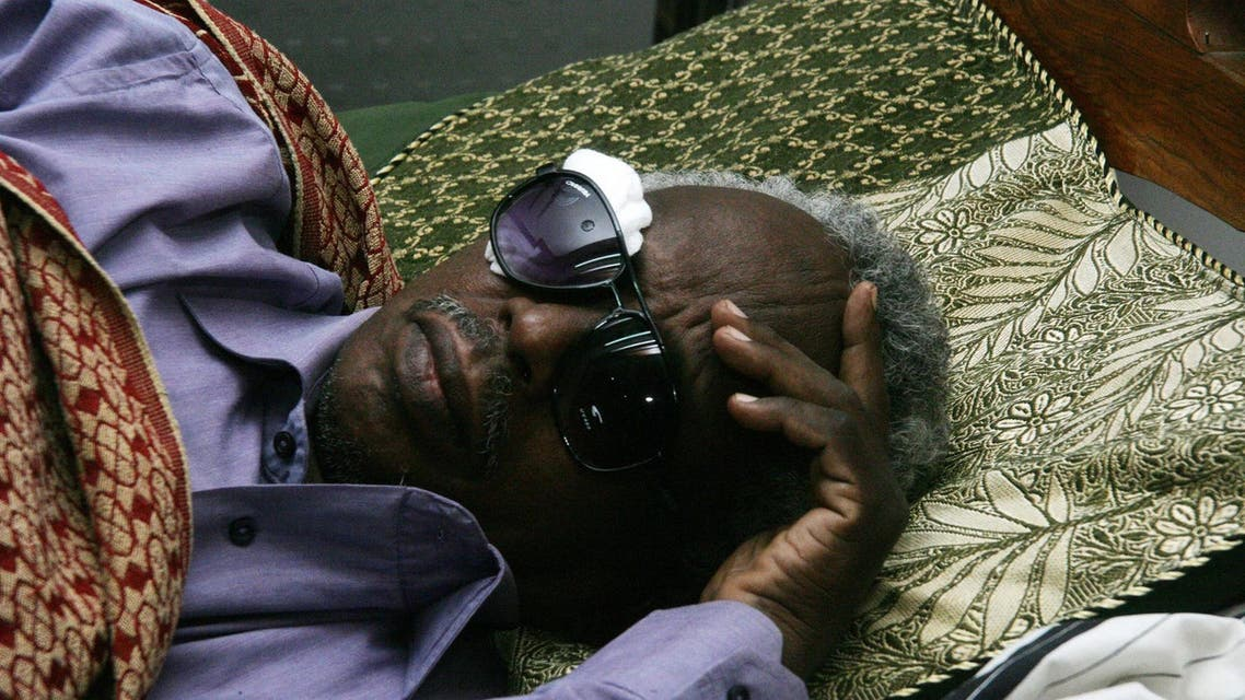 Osman Mirghani, chief editor of the Al-Tayar daily, lies on his bed after he was severely beaten by armed men who raided the offices of the Sudanese newspaper on July 24, 2014. (AFP)