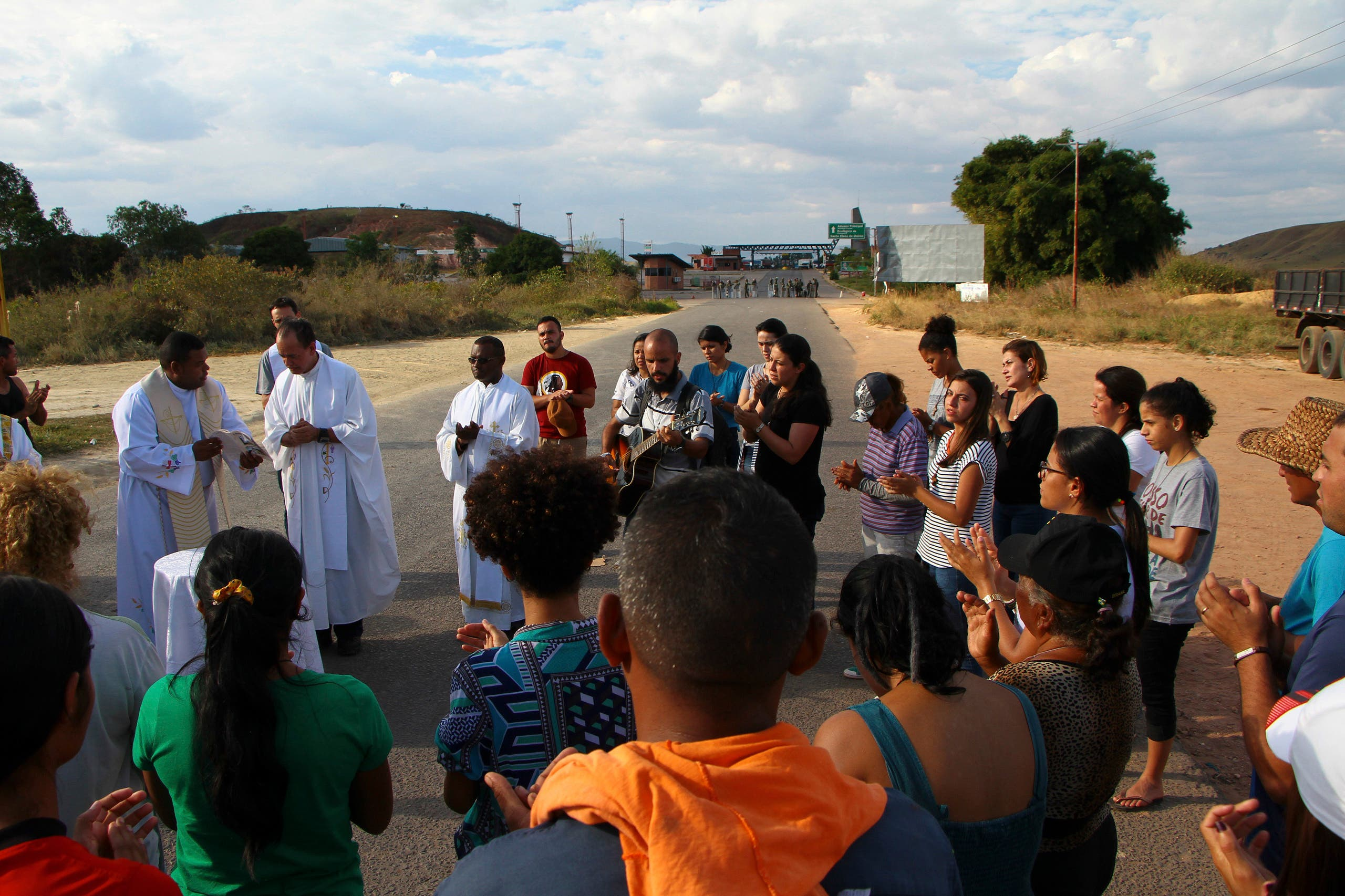 Venezuelans and Brazilians attend a Mass conducted by Venezuelan priests, next to a border checkpoint in Pacaraima, Roraima state, Brazil, Friday, Feb.22, 2019. Heightened tensions in Venezuela left a woman dead and a dozen injured near the border with Brazil on Friday, in the first deadly clash over the opposition's attempts to bring in emergency food and medicine that President Nicolas Maduro says isn't needed and has vowed to block (AP)