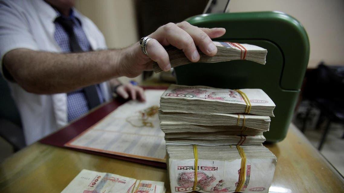A man counts Algerian Dinar banknotes in Algiers city, Algeria. (Reuters)