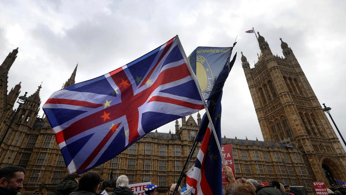 Anti-Brexit campaigners wave flags in front of parliament in London, Wednesday, Dec. 5, 2018. (AP)