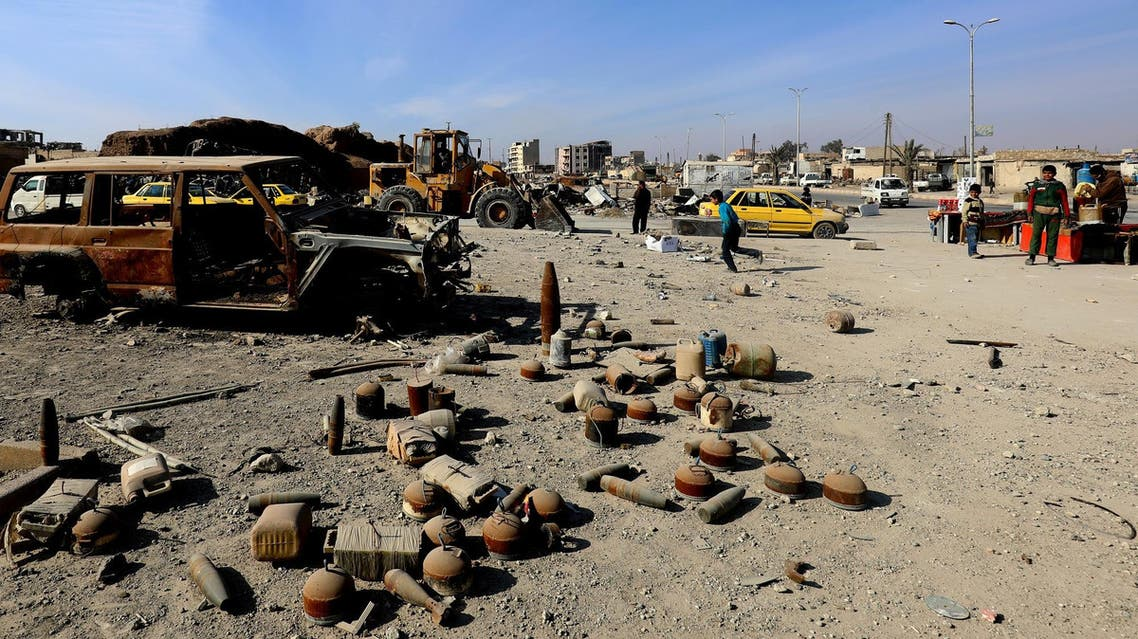 Shells and undetonated mines strewn near a burnt-out vehicle on a street in Syria's Raqa that were left by ISIS. (File photo: AFP)