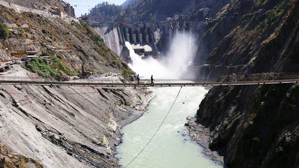 Laborers walk on a bridge near the newly inaugurated 450-megawatt hydropower project at Chanderkote. (Reuters)
