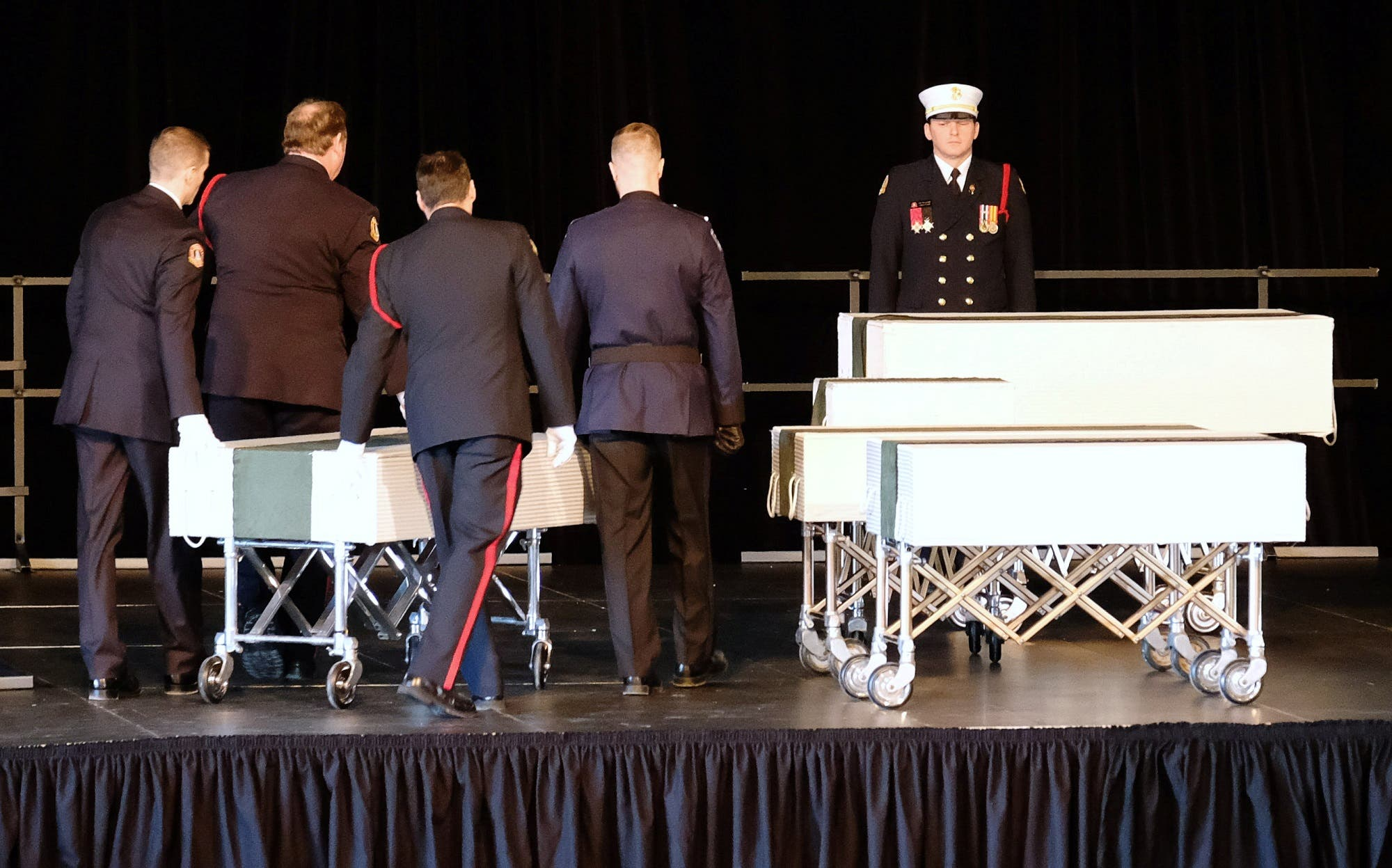 Halifax Regional Police and Fire Honour Guard move one of the caskets of the Barho family children during their funeral service. (Reuters)