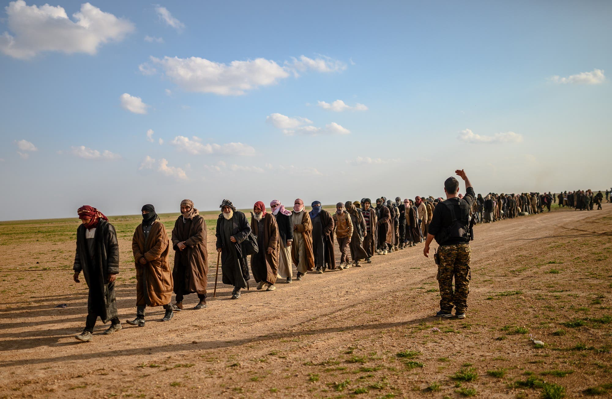 Men suspected of being ISIS fighters wait to be searched by members of the SDF after leaving the group's last holdout of Baghouz in Syria, on February 22, 2019. (AFP)