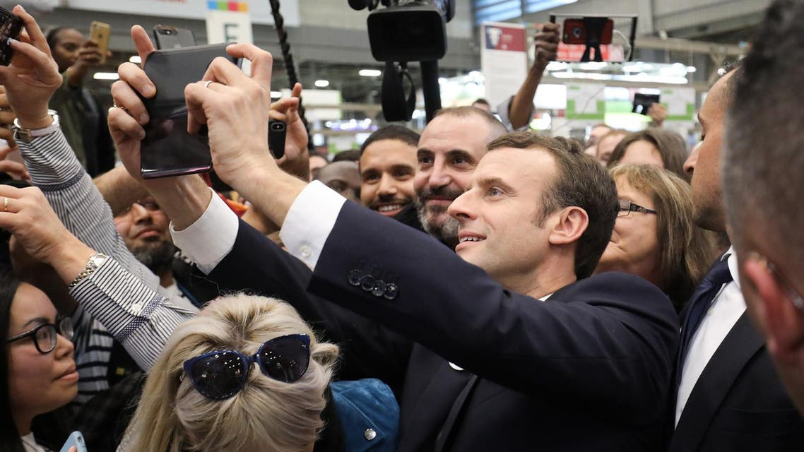 Emmanuel Macron poses for a selfie with visitors during the 56th International Agriculture Fair in Paris, on February 23, 2019. (AFP)