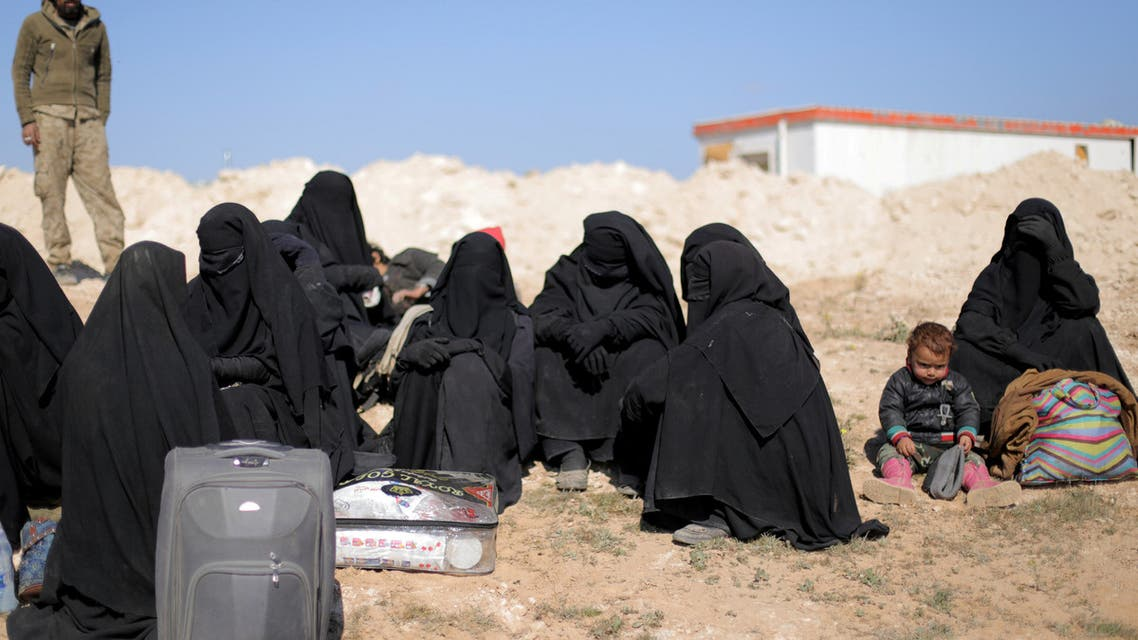 FILE PHOTO: Women sit together with their belongings near Baghouz, Deir Al Zor province, Syria February 12, 2019. Picture taken February 12, 2019. REUTERS/ Rodi Said/File Photo